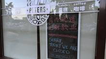 A notice indicating the closing of the shop is placed behind the window of the coffee shop owned by Canadians Kevin Garratt and Julia Garratt in Dandong, China, on Aug. 5, 2014. China is investigating the Canadian couple for alleged theft of state secrets. (REUTERS)
