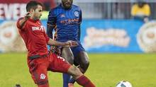 Toronto FC's Steven Beitashour, left, kicks the ball away from New York City FC's Stiven Mendoza in Toronto, Wednesday May 18, 2016. (Mark Blinch/The Canadian Press)
