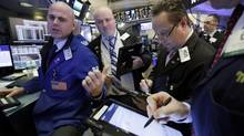 Specialist Mark Fitzgerald, left, works with traders at his post on the floor of the New York Stock Exchange, Tuesday, Jan. 10. (Richard Drew/AP)