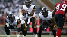 Hamilton Tiger-Cats' quarterback Henry Burris, centre, calls for the ball as he keeps his eye on Calgary Stampeders' Cordarro Law, right, during first quarter CFL football action in Calgary, Alta., Friday, Sept. 13, 2013. (JEFF MCINTOSH/THE CANADIAN PRESS)