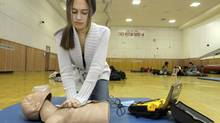 In this Jan. 10, 2011, photo, student Olivia Frierson presses contact pads from an AED machine onto a CPR mannequin during a CPR training class at Shaker Heights High School in Shaker Heights, Ohio. The Canadian Association of Emergency Physicians, representing emergency room doctors, is calling for mandatory CPR training for all Canadian high school students. (Amy Sancetta/AP)