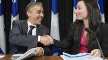 Quebec Finance Minister Nicolas Marceau, left and Quebec Natural Resources Minister Martine Ouellet, shake hands after they presented a plan to raise mining royalties. (Clement Allard/THE CANADIAN PRESS)