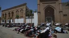 Muslim worshipers pray outsise a mosque in noon prayers in Kashgar, China, Friday, July 10, 2009. (Elizabeth Dalziel/AP)