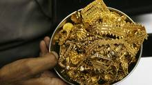 A trader holds gold jewellery at a shop in Mumbai November 3, 2009. (PUNIT PARANJPE)
