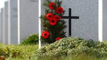 Poppies adorn a headstone at the Canadian Military Cemetery in Ottawa. (Sean Kilpatrick/THE CANADIAN PRESS)
