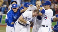 Toronto Blue Jays David Cooper (C) is mobbed by team mates after he drove in the game winning run in the eleventh inning of their American League MLB baseball game against the Chicago White Sox in Toronto August 13, 2012. (FRED THORNHILL/REUTERS)