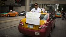 "Taxi driver Mubashar Jafri holds a sign that says ""Private should not outweigh public safety"" during a protest held by Taxi drivers against Uber in Toronto, Monday June 1, 2015. (Mark Blinch For The Globe and Mail)"