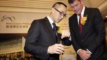 Lawrence Ho, left, co-chairman and chief executive officer of Melco Crown Entertainment, talks with James Packer, an Australian gambling tycoon and co-chairman of Melco Crown Entertainment, on March 15, 2013, during the signing deal with local partner Belle Corp for a casino project in Manila. (CHERYL RAVELO/Reuters)