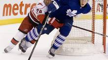 Toronto Maple Leafs defenceman Carl Gunnarsson (right) controls the puck despite pressure from Carolina Hurricanes Scott Walker during third period NHL action in Toronto on Tuesday, March 2, 2010. THE CANADIAN PRESS/Chris Young (CHRIS YOUNG)