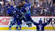 Maxim Lapierre #40 of the Vancouver Canucks celebrates with Alexander Edler #23, Manny Malhotra #27 and Kevin Bieksa #3 of the Vancouver Canucks after scoring a goal in the third period. (Rich Lam/2011 Getty Images)