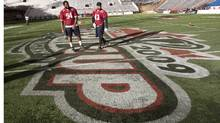 Jeff Robertshaw, left, and Guillaume Allard-Cameus of the Montreal Alouettes stand at centre field of McMahon Stadium during Wednesday's practice. (Paul Chiasson/Paul Chiasson/CP)