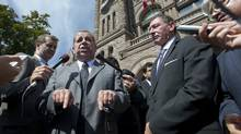Teacher's union officials and labour leaders speak to media outside Queen's Park in Toronto on Tuesday. (KEVIN VAN PAASSEN/THE GLOBE AND MAIL)