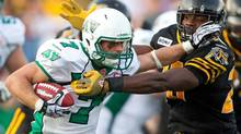 Saskatchewan Roughriders' Weston Dressler tries to break a tackle from Hamilton Tiger-Cats' Jamall Johnson during first half CFL action at Ivor Wynne Stadium in Hamilton, Ont., Friday, June 29, 2012. (Geoff Robins/THE CANADIAN PRESS)