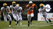 B.C. Lions' Andrew Harris, centre, outruns Edmonton Eskimos' J.C. Sherritt, from left, Julius Williams and Donovan Alexander for a 63-yard-touchdown during the second half of a CFL football game in Vancouver, B.C., on Friday Sept. 30, 2011. (DARRYL DYCK/THE CANADIAN PRESS/DARRYL DYCK/THE CANADIAN PRESS)