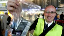 An airport employee displays a plastic bag after the new restrictions for liquids in hand luggage started at the airport in Frankfurt, central Germany, Monday, Nov. 6, 2006. The new EU rules limit passengers to carrying 100 milliliters (a fifth of a pint) of liquid per container on board planes. (MICHAEL PROBST/AP)