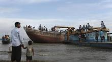 A Bangladeshi man stands with a child as others gather by the River Padma where a passenger ferry capsized Monday in Munshiganj district, Bangladesh, Tuesday, Aug. 5, 2014. (A.M. Ahad/AP)