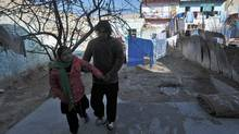 Twelve-year-old Tarana Akbari (L) walks in the yard with the help of her uncle outside her home in Kabul on December 10, 2011. (MASSOUD HOSSAINI/AFP/Getty Images/MASSOUD HOSSAINI/AFP/Getty Images)