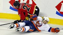 New York Islanders' Tim Wallace, right, crashes to the ice with Calgary Flames' Derek Smith during second period pre-season NHL hockey action in Calgary, Alta., Tuesday, Sept. 27, 2011. (Jeff McIntosh/THE CANADIAN PRESS)