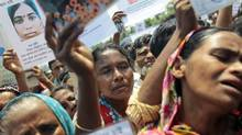 Bangladeshi hold up portraits of their missing relatives as they gather to offer prayers for the souls of the 1,127 people who died in the garment building structure collapse last month, in Savar, Bangladesh, on Tuesday, May 14, 2013. (A.M. Ahad/Associated Press)