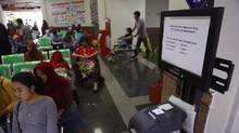 Patients wait near a queue number dispenser affected by 'WannaCry' attack at Dharmais Cancer Hospital in Jakarta, Indonesia, Monday, May 15, 2017. Global cyber chaos was spreading Monday as companies booted up computers at work following the weekend's worldwide ransomware cyberattack. (Dita Alangkara/AP)