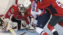 Windsor Spitfires Ryan Ellis (right) tries to control Moncton Wildcats Gabriel Bourque as he battles for the puck with Spitfires goaltender Troy Passingham during first period Memorial Cup hockey action in Brandon, Manitoba on Tuesday May 18, 2010. (Frank Gunn/THE CANADIAN PRESS)