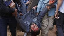 Anti-Mursi protesters carry a Muslim Brotherhood member after hitting him during clashes near the Muslim Brotherhood's national headquarters in Cairo's Moqattam district March 22, 2013. (STRINGER/REUTERS)