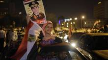 A supporter of presidential hopeful Abdel-Fattah el-Sissi, Egypt's former military chief, holds his poster and a national flag during a celebration at Tahrir Square in Cairo, Egypt, Thursday, May 29, 2014. (Amr Nabil/AP)