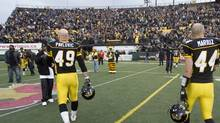 Hamilton Tiger-Cats linebacker Ray Mariuz (44) and fullback Robert Pavlovic (47) walk off the field after losing 34-27 in overtime to the B.C. Lions in CFL Eastern Conference semi-final action in Hamilton, Ontario on Sunday, November 15, 2009.THE CANADIAN PRESS/Frank Gunn (Frank Gunn)