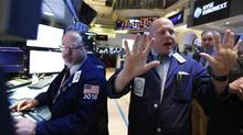 Specialist trader Michael O'Connor gives a price to traders on the floor at the New York Stock Exchange, April 3, 2013. (Brendan McDermid/Reuters)