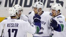 Vancouver Canucks players celebrate Alexander Edler's (2nd R) goal during the second period of their NHL hockey game against the St. Louis Blues in St. Louis, Missouri, April 16, 2013. (SARAH CONARD/REUTERS)