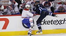 Winnipeg Jets forward Evander Kane takes out Montreal Canadiens defenseman Jaroslav Spacek in the first period of the inaugural game at the MTS Centre in Winnipeg, Sunday. (JOHN WOODS/The Canadian Press)
