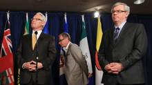 Saskatchewan Premier Brad Wall, centre, walks in behind British Columbia Premier Gordon Campbell, left, and Manitoba Premier Greg Selinger, right, while addressing reporters before the start of the Western Premiers' Conference in Vancouver, B.C., on Tuesday June 15, 2010. (Darryl Dyck/The Canadian Press)