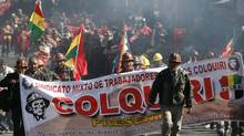 Workers from Colquiri mine who support Bolivian President Evo Morales participate in a march in La Paz. Thousands of farmers arrived in La Paz to support Morales after the police mutinied over low wages and sparked a political crisis that lasted five days, according to local media. (ENRIQUE CASTRO-MENDIVIL/Reuters)