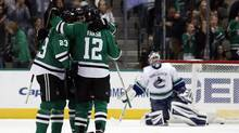Dallas Stars' Esa Lindell (23), Jamie Oleksiak (5) and Radek Faksa (12) celebrate after Faksa scored against Vancouver Canucks goalie Ryan Miller (30) during the second period of an NHL hockey game, Friday, Nov. 25, 2016, in Dallas. (Mike Stone/AP)