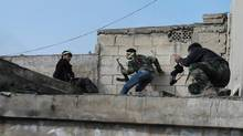 Members of the Free Syrian Army take up position with their weapons during clashes with forces loyal to Syria's President Bashar al-Assad, in the old city of Aleppo March 2, 2013. Picture taken March 2, 2013. (STRINGER/REUTERS)