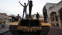 "Anti-Morsi protesters stand on a military tank in front of the presidential palace in Cairo, December 8, 2012. Egypt's military, stepping into a crisis pitting Islamist President Mohamed Mursi against opponents who accuse him of grabbing excessive power, said on Saturday only dialogue could avert ""catastrophe."" (AMR ABDALLAH DALSH/REUTERS)"
