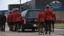 The hearse carrying RCMP Constable Dave Ross, a dog handler, is followed by his police dog, Danny, along with a Mountie carrying his Stetson in a parade in Moncton on June 10, 2014. (FRED LUM/THE GLOBE AND MAIL)