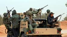Members of the Tunisian military patrol a road near the Libyan border on March 10, 2016 in Bouhamed, as they hunt jihadists in the area. (FATHI NASRI/AFP/Getty Images)