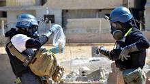 Members of the UN investigation team take samples in the Damascus countryside of Ain Terma in August. Syria is believed by experts to have chemical warfare agents scattered over several dozen sites across the country. (Associated Press)