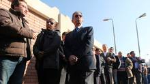Presidential candidate Amr Moussa (C) waits to cast his vote outside a polling station during parliamentary elections in Cairo November 28, 2011. (Amr Abdallah Dalsh/Reuters)
