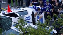 A Vancouver Canucks fan jumps from a police car that was overturned by rioters following the Vancouver Canucks defeat by the Boston Bruins in the NHL Stanley Cup Final in Vancouver, June 15, 2011. (Darryl Dyck/ The Canadian Press/Darryl Dyck/ The Canadian Press)