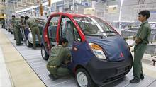 Employees work inside Tata Motors Ltd.'s Nano car plant at Sanand in Gujarat, India. (AMIT DAVE/REUTERS)