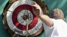 Brad Laughlin, of Vancouver, hits the bullseye during the axe toss competition at the King of the Klondike competition in Edmonton on Saturday Aug. 27, 2005. (Jason Franson/CP)