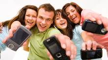 Four teenagers showing cell phones (Jupiterimages/Getty Images)