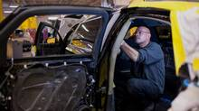 A worker installs interior armor plating to a stretch limousine at the INKAS Corp. manufacturing facility in Toronto, Ontario, Canada, on Monday, Nov. 9, 2015. (James MacDonald/Bloomberg)