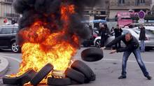 A striking French taxi driver burns tires during a national protest about competition from private car ride firms like Uber, in Marseille, France, January 26, 2016. (JEAN-PAUL PELISSIER/REUTERS)