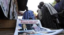 People gather around a street news stand to read newspapers in Bamako January 18, 2013. The headline of the newspaper which lays on a table reads, 'Thank you France, Thank you Franois Hollande,' as President Hollande has pledged that French troops will stay until stability returns to Mali. (ERIC GAILLARD/REUTERS)