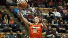 Syracuse's Tyler Ennis goes up for a basket against Virginia Tech's C.J. Barksdale during the first half of an NCAA college basketball game Tuesday, Jan. 7, 2014, in Blacksburg, Va. (Associated Press)