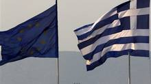 A Greek, right, and an EU flag fly over the Greece's Finance Ministry in Athens. (© Yannis Behrakis / Reuters/REUTERS)