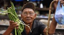 A man holds vegetables as he tries to bargain with the vendor at a market in Jakarta January 4, 2011. The Central Statistics Agency said on Monday that Indonesia's inflation for 2010 came in at 6.96 percent due to rising food prices. (Beawiharta/Reuters/Beawiharta/Reuters)
